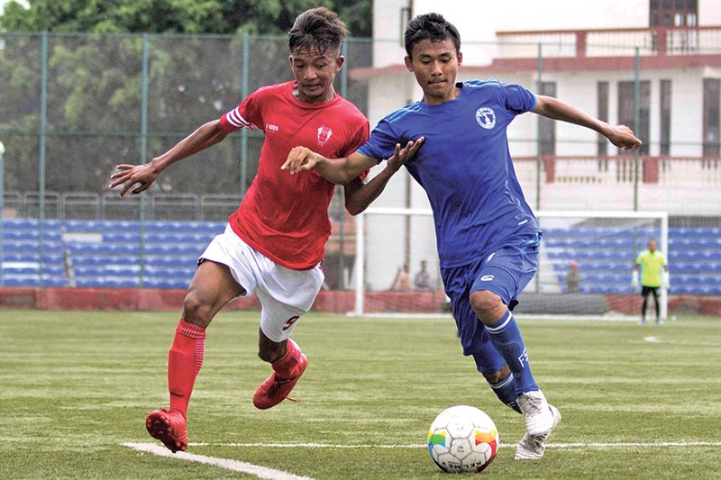 Sushan Blon (left) of Brigade Boys Club vies for the ball against Nepal Police Club player during their Lalit Memorial U-18 Football Championship matches at the ANFA Complex, Satdobato in Lalitpur on Tuesday. Photo: THT