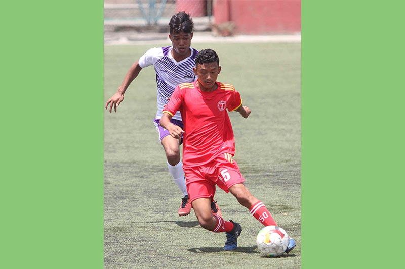 Amrit Rai of NPC beats past a SYC player during their Lalit Memorial U-18 Football Championship match in Lalitpur on Thursday, July 4, 2019. Photo: THT