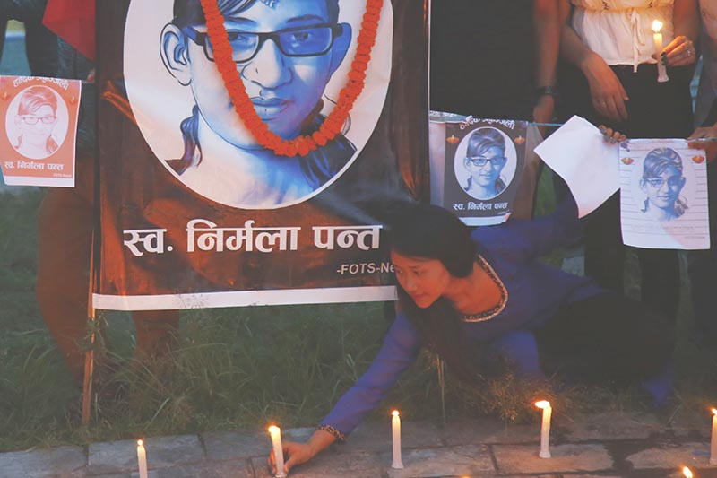 A girl placing candles in front of a portrait of Nirmala Panta during a candle-light vigil to mark one year since she was raped and murdered, in Kathmandu, on Friday, July 26, 2019. Photo: Skanda Gautam/THT