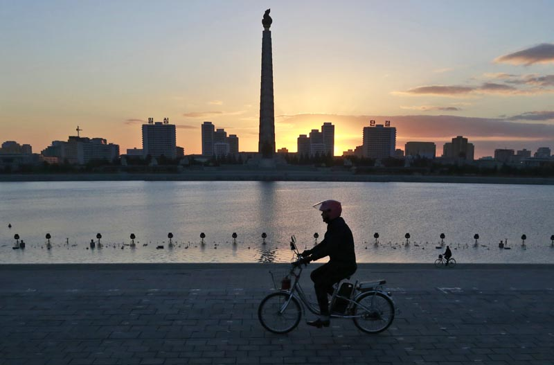 FILE - In this October 27, 2018 file photo, a man rides his electric bike as the Tower of the Juche Idea is silhouetted agains the sunrise in Pyongyang, North Korea. Photo: AP