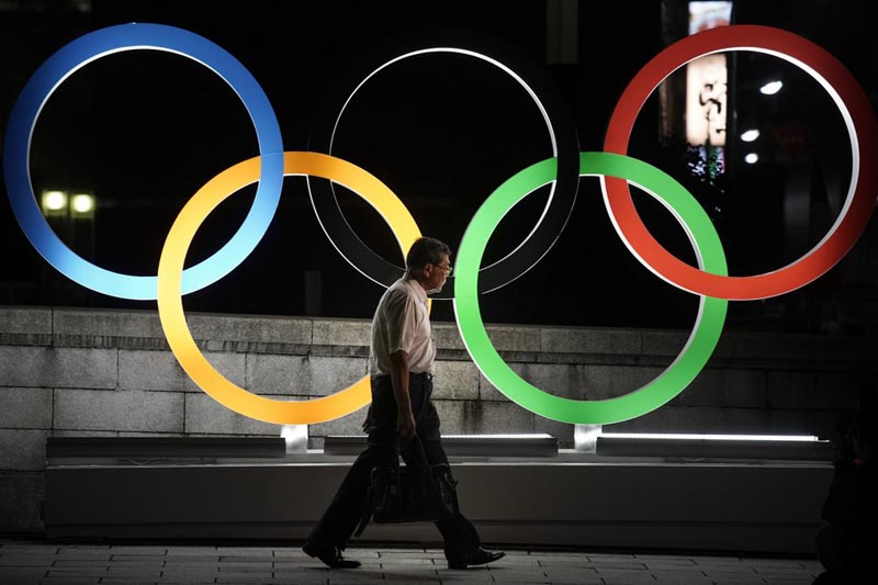 A man walks past the Olympic rings Tuesday, July 23, 2019, in Tokyo, as Japan marks a year-to-go until hosting the summer games with Olympic medals being unveiled Wednesday as part of daylong ceremonies around the Japanese capital.