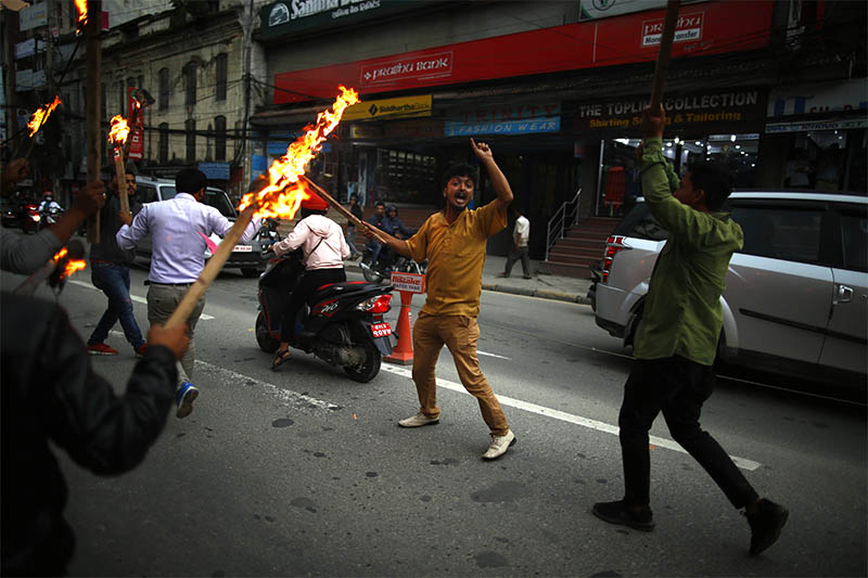 Cadres of Student Union, the wing of the main opposition Nepali Congress, stage a torch protest against the government's decision to put on hold its decision to carry out pesticide testing for vegetables and fruits imported from India in Kathmandu, on Thursday, July 11, 2019. Photo: Skanda Gautam/THT