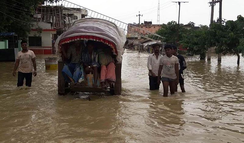 Locals heading towards their destination through a flooded street in Gaur, Rautahat. Photo: THT