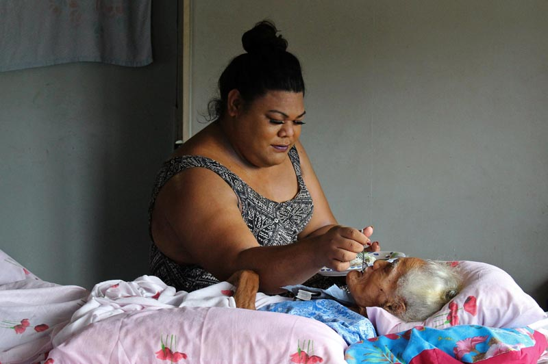 Samoan fa'afafine Keyonce Lee Hang feeds her grandmother in the family home on the island of Upolu, Samoa, July 14, 2019. Photo: Reuters
