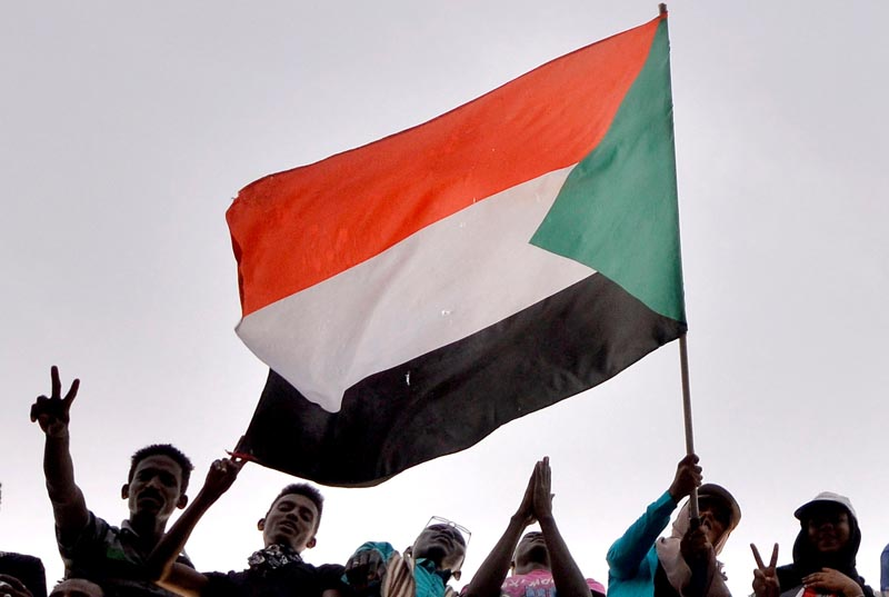 FILE: Sudanese demonstrators wave the national flag as they attend a protest rally demanding Sudanese President Omar Al-Bashir to step down, outside Defense Ministry in Khartoum, Sudan, April 10, 2019.Photo: Reuters