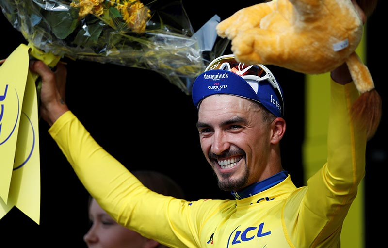 Deceuninck-Quick Step rider Julian Alaphilippe of France celebrates on the podium, wearing the overall leader's yellow jersey after winning the Tour de France The 215-km Stage 3 from Binche to Epernay, on July 8, 2019. Photo: Reuters