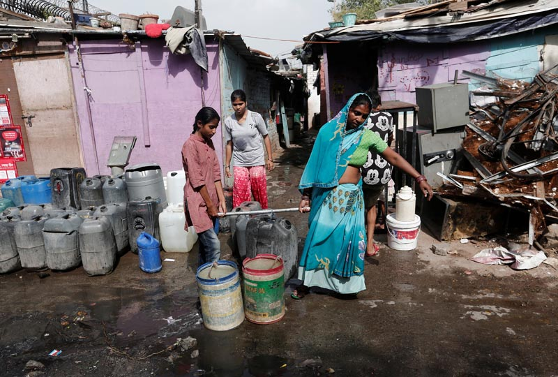 A woman and her daughter carry a container after filling it with drinking water from a municipal tanker in New Delhi, India, June 28, 2019. Picture taken June 28, 2019. Photo: Reuters