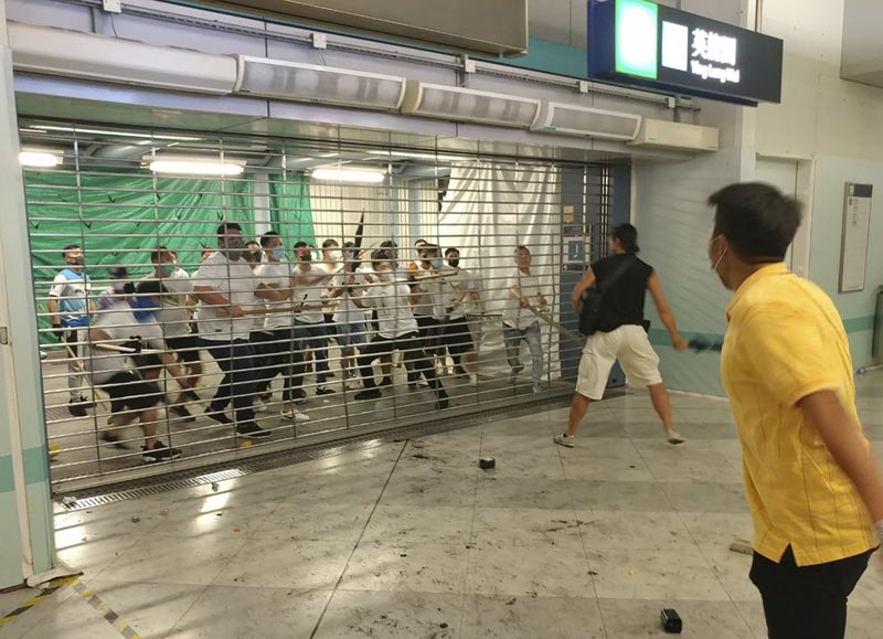 In this Sunday, July 21, 2019, photo, men in white shirts armed with metal rods and wooden poles attack commuters at a subway station in New Territory in Hong Kong. Photo: AP