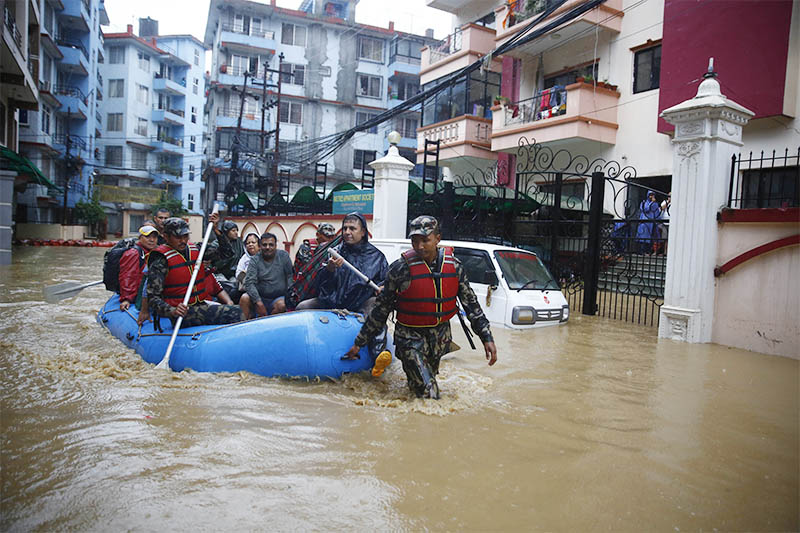 FILE - Army personnel rescuing people in raft from ground floors of houses along an inundated road following heavy rainfall, in Kathmandu, on Friday., July 12, 2019. Photo: Skanda Gautam/THT