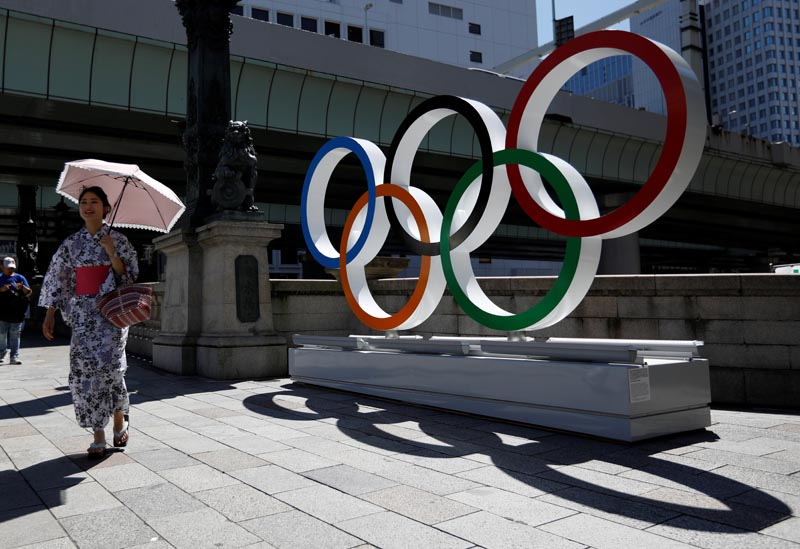 FILE - A woman wearing the yukata, or casual summer kimono, walks past Olympic rings displayed at Nihonbashi district in Tokyo, Japan August 5, 2019. Photo: AP