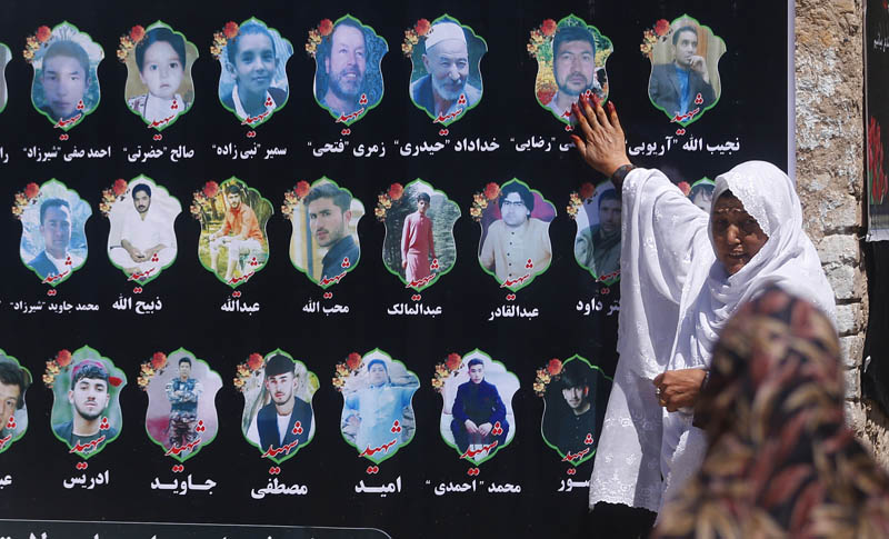 An Afghan woman cries as she touches a banner displaying photographs of victims of the Dubai City wedding hall bombing during a memorial service in Kabul, Afghanistan, Tuesday, August 20, 2019. Photo: AP