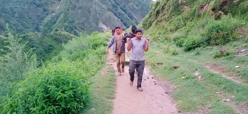 Badure Damai of Badimalika Municipality-7, Bajura being taken to the bus park to travel to Kathmandu for his treatment. Photo: Prakash Singh/THT