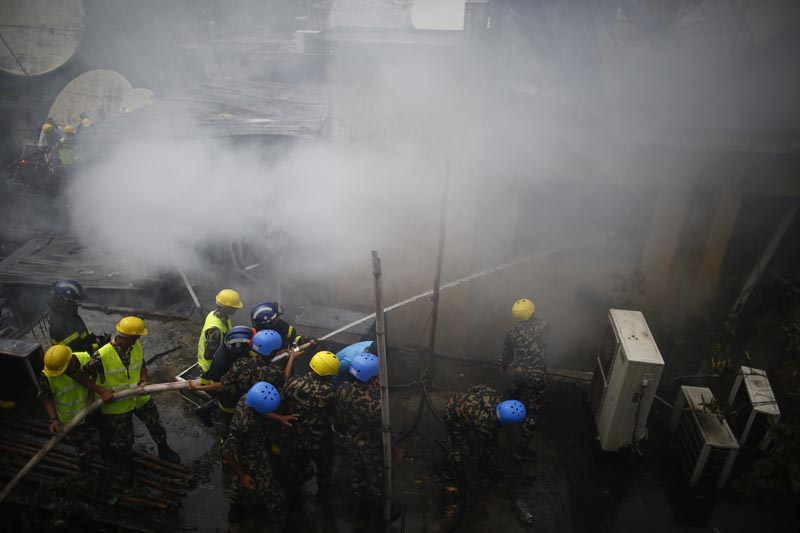 Firefighters along with security personnel make efforts to douse the fire that engulfed a building of Subisu Cablenet Pvt Ltd, located in Baluwatar, Kathmandu, on Wednesday, August 7, 2019. Photo: Skanda Gautam/THT