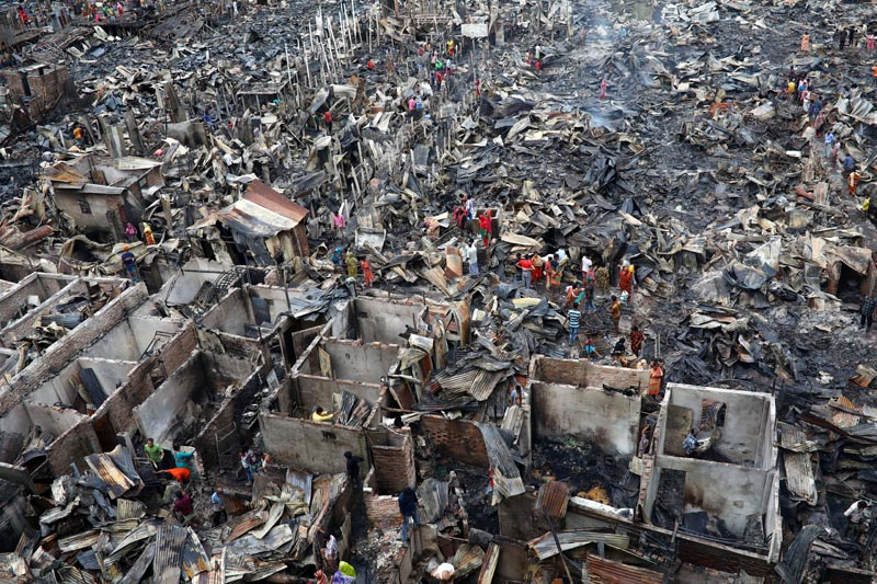 Slum dwellers are seen searching for their belongings from ashes after fire broke out on their shelters in Dhaka, Bangladesh, August 17, 2019. Photo: Reuters
