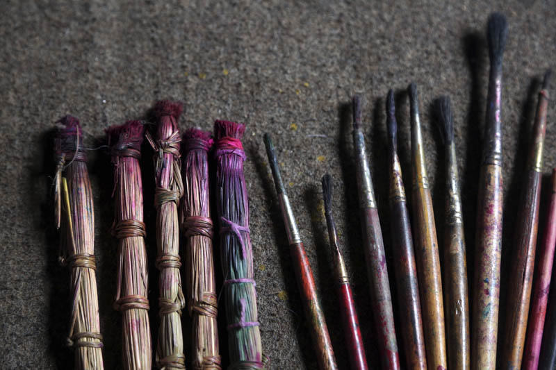 Handmade traditional brushes, left, are lined up along with modern paint brushes at the residence of Chitrakar couple Tej Kumari and Purna, in Bhaktapur, Nepal. July 31, 2019. Photo: AP