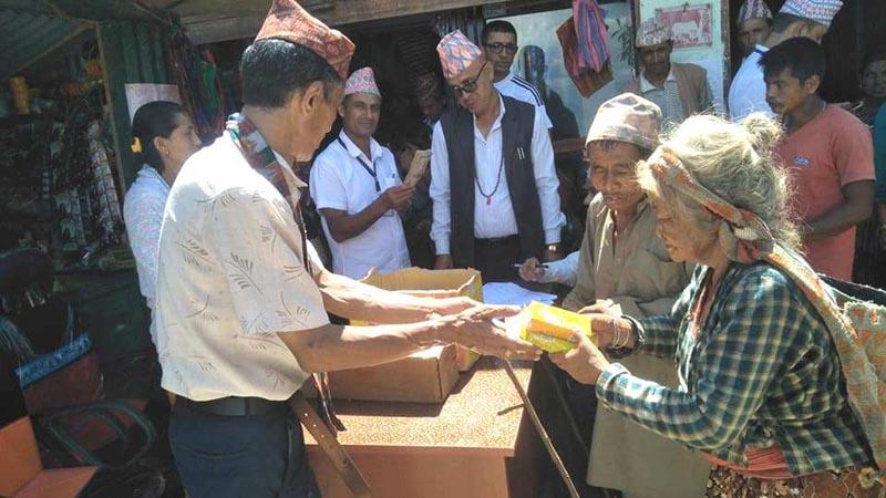 Chairperson of Arun Rural Municipality Gajendra Bahadur Karki providing food items to the elderly people of the rural municipality during a programme on Tuesday, August 13, 2019. Photo: Niroj Koirala/THT