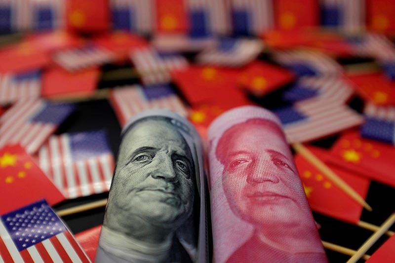 FILE -  A US dollar banknote featuring American founding father Benjamin Franklin and China's yuan banknote featuring late Chinese chairman Mao Zedong are seen among US and Chinese flags in this illustration picture taken May 20, 2019. Photo: Reuters