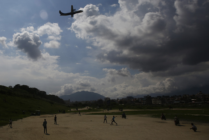 Youngsters silhouetted play cricket on an open ground as an aircraft takes flight in Kathmandu, Nepal on Saturday, August 10, 2019. Photo: Skanda Gautam/THT