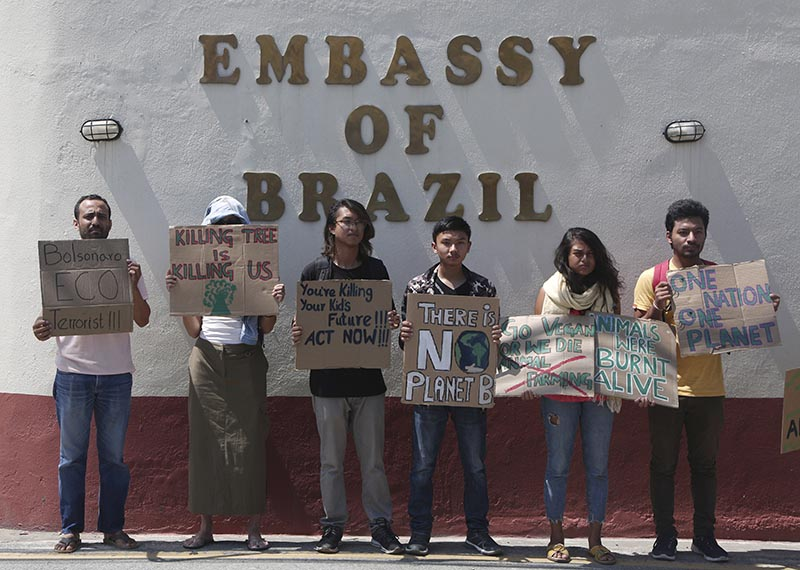 Nepali activists hold placards expressing concern over fires burning across the Amazon region as they gather outside the Embassy of Brazil in Kathmandu, on Monday, August 26, 2019. Brazilian government satellite monitors have recorded more than 41,000 fires in the Amazon region so far this year — with more than half of those coming this month alone. Photo: AP