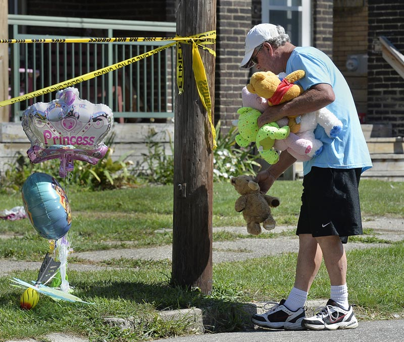 Paul Laughlin (57) places stuffed animals on Sunday, August 11, 2019 outside a home at 1248 West 11th Street in Erie, Pennsylvania, where multiple people died in an early-morning fire. Photo: Greg Wohlford/Erie Times-News via AP