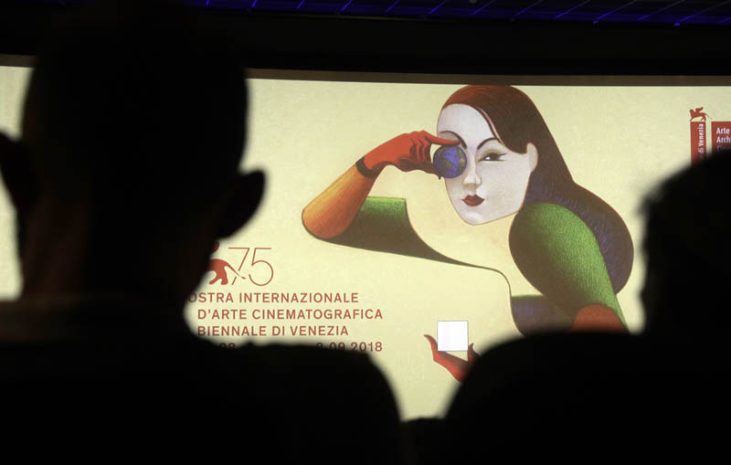 Journalists are silhouetted against the logo presenting the 75th edition of the festival, during its presentation in Rome, Wednesday, July 25, 2018. Photo: AP/File