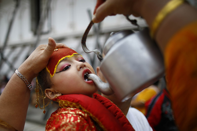 A girl is offered milk during a procession to mark Gai Jatra or the Cow Festival, in Kathmandu, on Friday, August 16, 2019. Locals mark the festival to wish peace for their deceased family members from preceding years. Photo: Skanda Gautam/THT