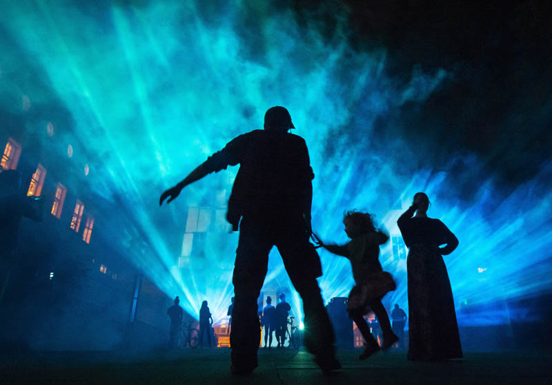 Visitors stand in front of a facade projection during the Genius Loci Festival in Weimar, Germany, Sunday, August 11, 2019. The Genius Loci Weimar is an annual festival for multimedia facade projections and takes place from August 9 to August 11 in the central German city. The festival will feature a contemporary building as a place of illumination and performance. Photo: AP