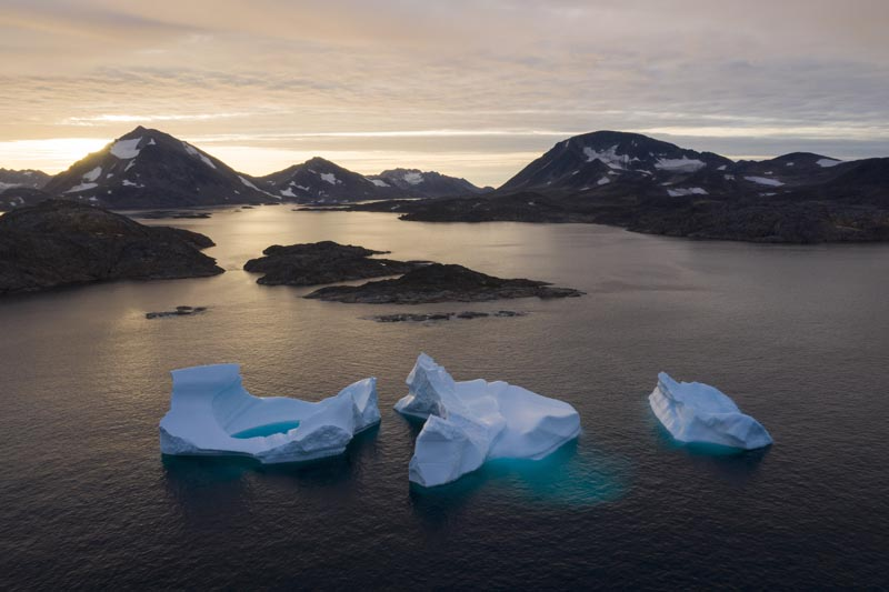 In this August 16, 2019, photo, large Icebergs float away as the sun rises near Kulusuk, Greenland. Photo: AP