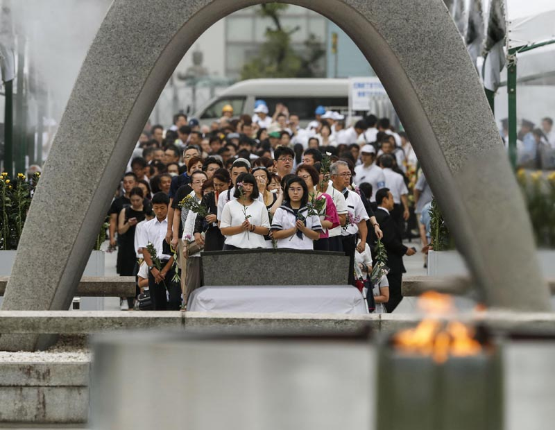 People pray for the atomic bomb victims in front of the cenotaph at the Hiroshima Peace Memorial Park in Hiroshima, western Japan during a ceremony to mark the 74th anniversary of the bombing Tuesday, August 6, 2019. Photo: Kyodo News via AP