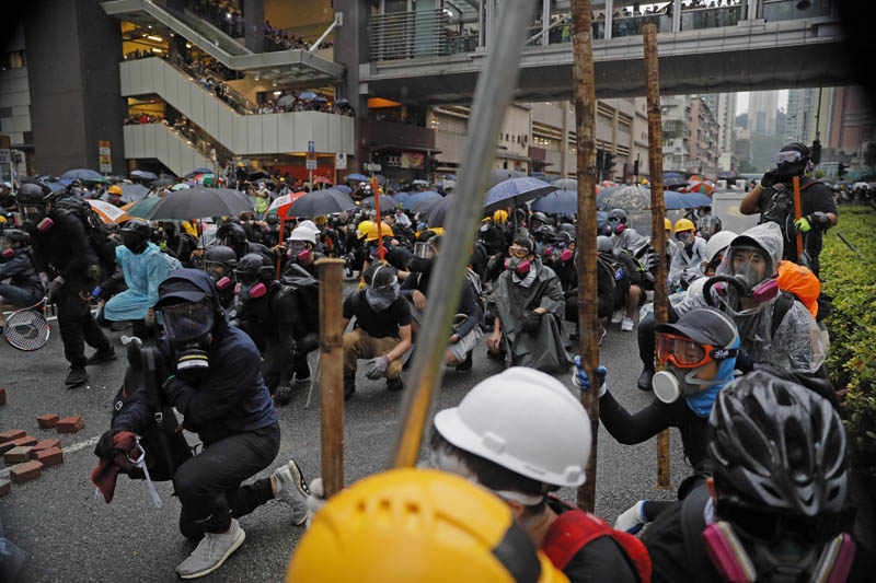 Protesters crouch behind a barricade during a protest in Hong Kong, Sunday, August 25, 2019. Photo: AP