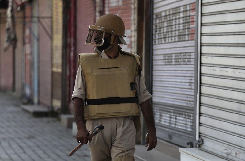In this Thursday, August 22, 2019 photo, a Kashmiri policeman guards outside a closed shop in Srinagar, Indian-controlled Kashmir. Photo: AP