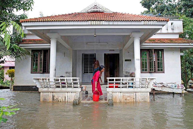 A woman clears out the water from her flooded house at Paravur on the outskirts of Kochi, in the southern state of Kerala, India August 11, 2019. Photo: Reuters