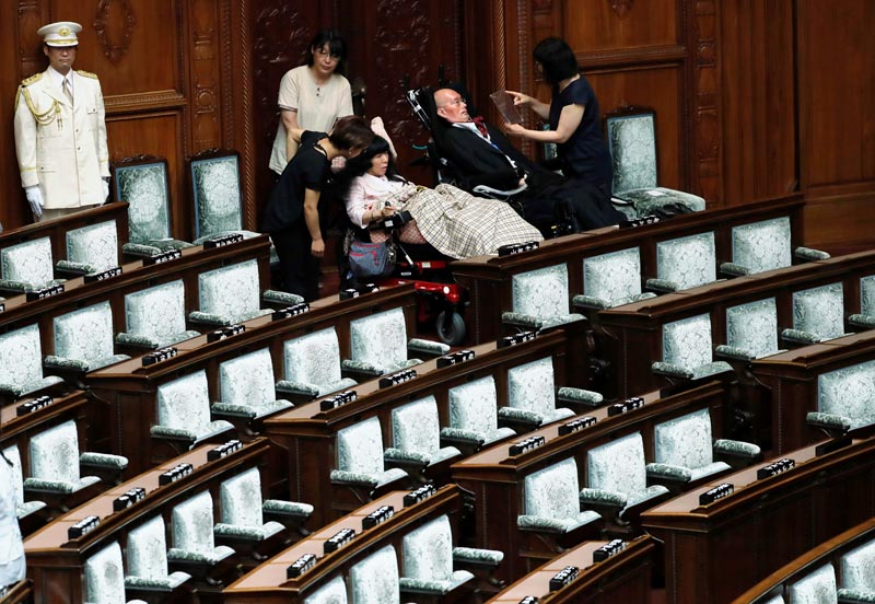 Reiwa Shinsengumi party's disabled lawmaker Yasuhiko Funago, who has amyotrophic lateral sclerosis (ALS), and Eiko Kimura, who has cerebral palsy, prepare to leave the hall after attending the opening of an extraordinary session of parliament in Tokyo, Japan, August 1, 2019. Photo: AP