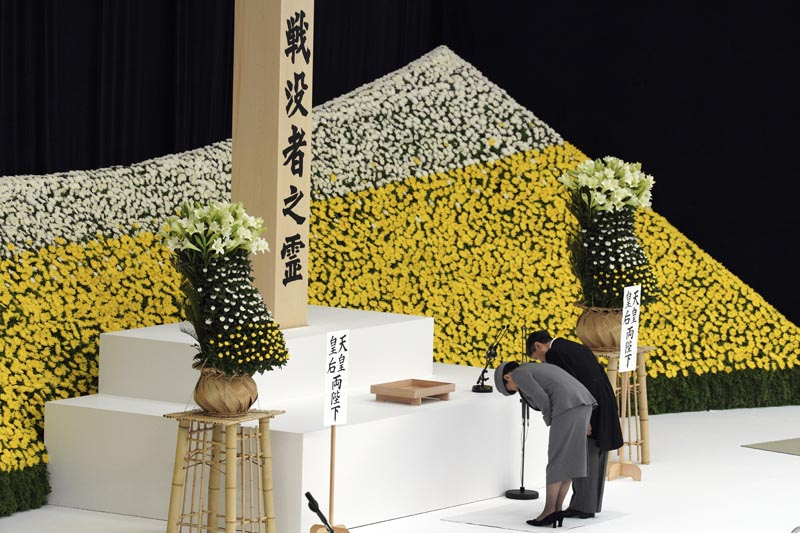 Japanese Emperor Naruhito, accompanied by Empress Masako bows before the main altar decorated with huge bank of chrysanthemums during a memorial service at Nippon Budokan Martial Arts Hall in Tokyo Thursday, August 15, 2019.  Japan marked Thursday the 74th anniversary of the end of World War II. Photo: AP