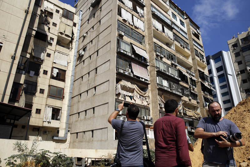 Journalists take pictures of the 11th-floor building that houses Hezbollah's media office as well as nearby buildings suffered minor damage and broken glass in a southern suburb of Beirut, Lebanon, Sunday, August 25, 2019. Photo: AP