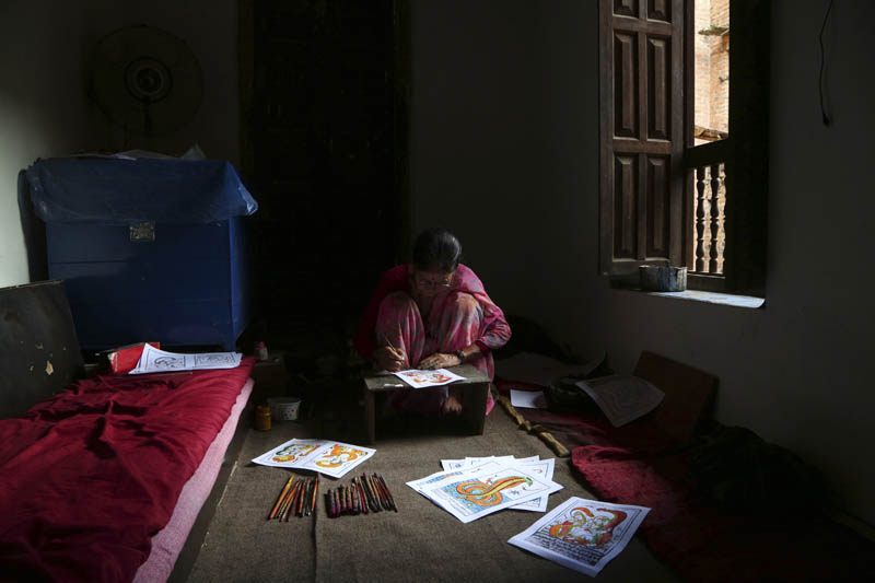 Tej Kumari Chitrakar makes traditional paintings ahead of Naag Panchami festival at her residence in Bhaktapur, Nepal, July 31, 2019. Photo: AP