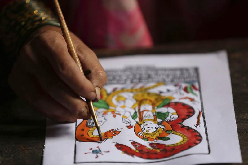 Tej Kumari Chitrakar makes a traditional painting ahead of Naag Panchami festival at her residence in Bhaktapur, Nepal, July 31, 2019. Photo: AP