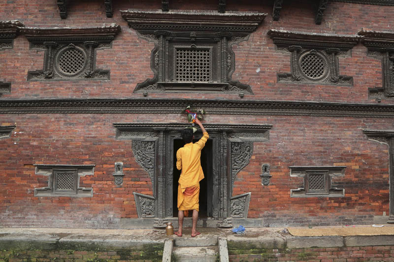A Nepali priest displays a machine made painting above the door of a temple during Naag Panchami festival in Bhaktapur, Nepal, August 5, 2019. Photo: AP