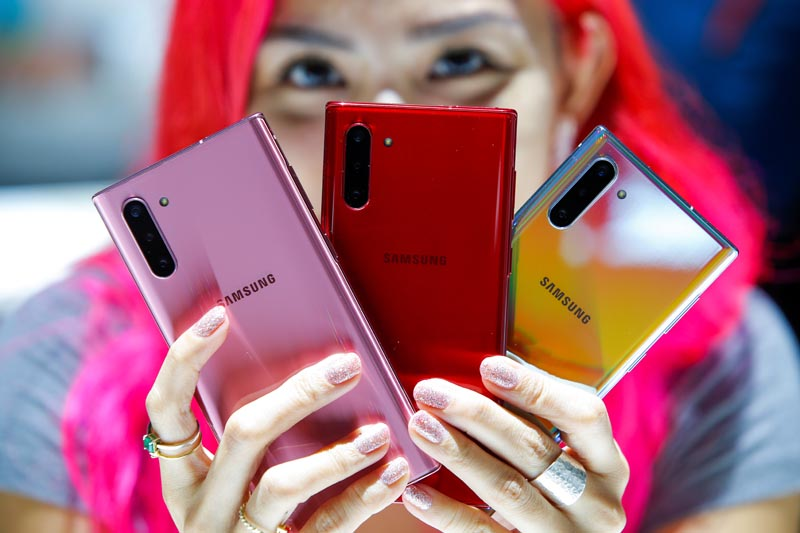 A woman holds different colored models of the Samsung Galaxy Note 10 while people test new devices during the launch event of the Galaxy Note 10 at the Barclays Center in Brooklyn, New York, US, August 7, 2019. Photo: Reuters