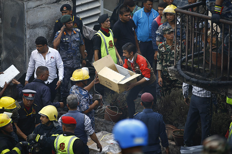 Staffers of Subisu, the internet service provider, recover items after the building caught fire, in Baluwatar, Kathmandu, on Wednesday, August 07, 2019. Photo: Skanda Gautam/THT