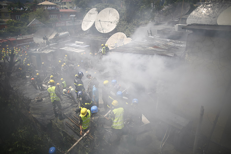 Firefighters and security personnel from Nepal Police, Armed Police Force of Nepal and Nepal Army make efforts to douse the fire and salvage items in Subisu, Baluwatar, Kathmandu, on Wednesday, August 07, 2019. Photo: Skanda Gautam/THT
