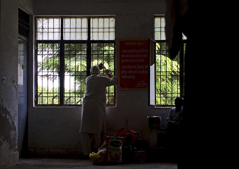 A Kashmiri man holds on to iron grills of a window as he awaits his turn to meet his son at Agra Central Jail in Agra, India, Friday, Sept. 20, 2019. Photo: AP