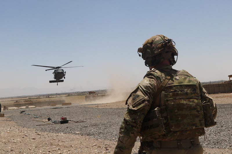A US soldier assigned to the Headquarters and Headquarters Battalion, 1st Armored Division watches as a UH-60 Blackhawk Helicopter prepares to land during an advise and assistance mission in southeastern Afghanistan, August 4, 2019. Photo: Alejandro Licea/US Army/Handout via Reuters
