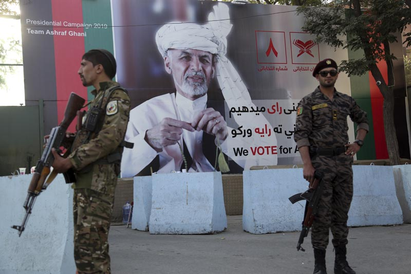 Afghan security forces stand guard in front of an election poster for presidential candidate Ashraf Ghani in Kabul, Afghanistan, Monday, Sept 23, 2019. Photo:AP