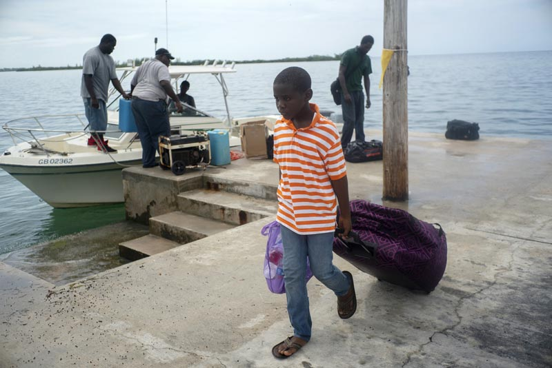 A child evacuated from a nearby Cay due to the danger of floods drags his suitcase when he arrives on a ship at the port before the arrival of Hurricane Dorian in Sweeting's Cay, Grand Bahama, Bahamas, Saturday, August 31, 2019. Photo: AP