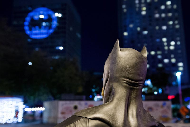 A man dressed as Batman looks up towards the Batman signal projected onto a building to celebrate Batman Day in Montreal, Saturday, September 21, 2019. Photo: AP