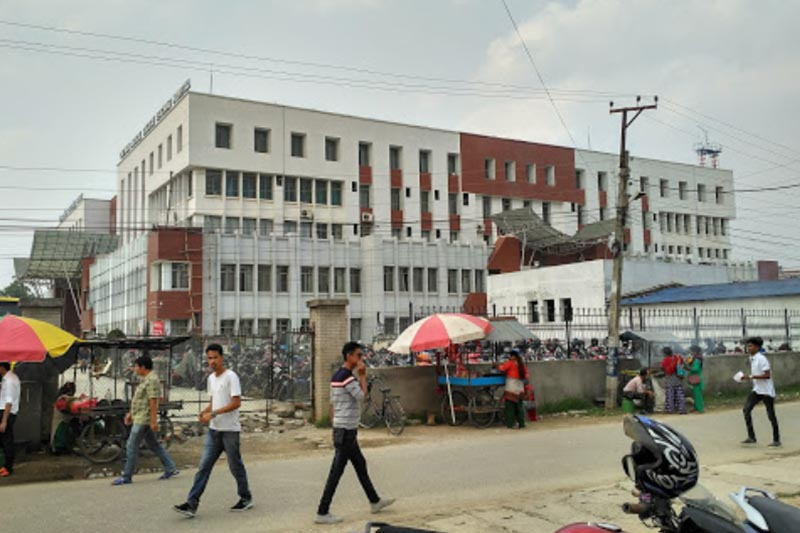 People walk down the road in front of Chitwan Medical College Teaching Hospital in Bharatpur Metropolis, Chitwan district, in May 2018. Photo courtesy: Amit Ghimire