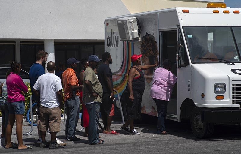People line up to buy pre-paid cell phone cards, for sale from a mobile Aliv office, after the passing of Hurricane Dorian in Freeport, Bahamas, Wednesday on Sept. 11, 2019.Photo: AP