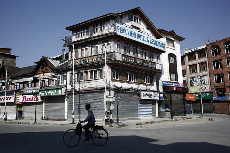 FILE: A man rides a bicycle past the closed shops and hotels during restrictions, after scrapping of the special constitutional status for Kashmir by the Indian government, in Srinagar, August 25, 2019. Photo: Reuters