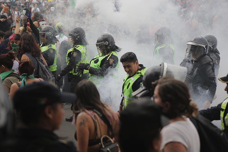 A cloud of smoke engulfs police after they put out a fire started by protesters during a women's rights protest in Mexico City on Saturday Sept. 28, 2019. Photo: AP